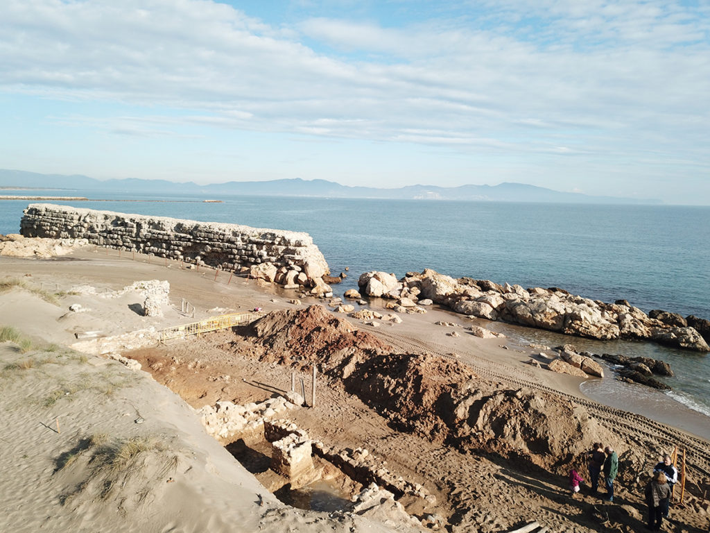 Vista aèria de l'excavació realitzada a la platja d'Empúries l'any 2019. Les restes descobertes en aquest sector conformaven l'illa d'edificacions de l'extrem nord-est de la ciutat grega. Al fons, l'espigó del port construït al segle II aC.