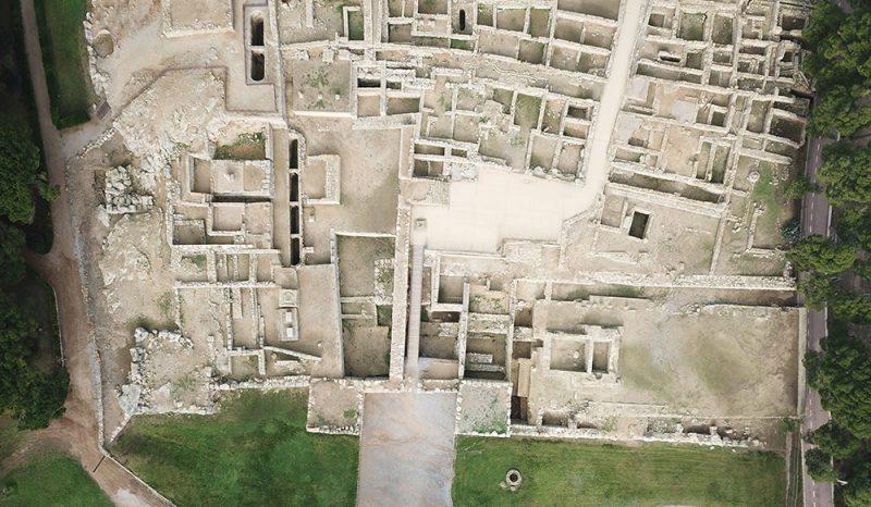 Figura 13. Vista aèria del sector meridional de la ciutat grega d'Empúries, ocupat pels edificis religiosos de la ciutat. A la banda dreta s'aprecia la terrassa baixa ocupada per un temple i les restes del porticat (Arxiu MAC-Empúries).