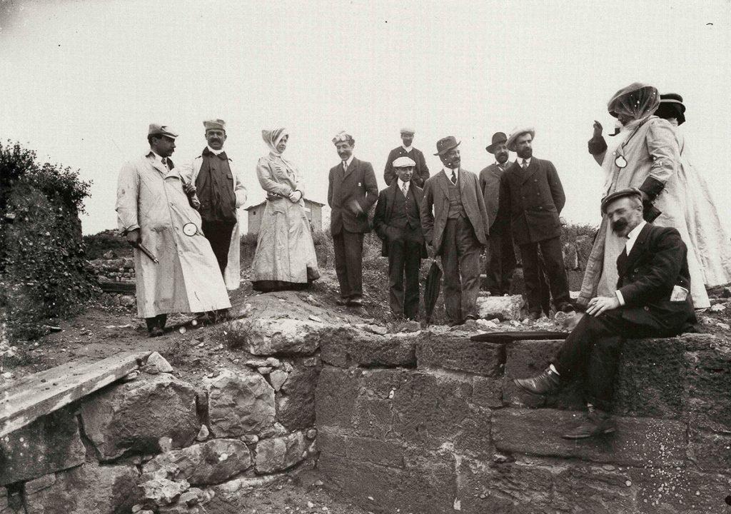 Figura 2. Visita dels membres del Centre Excursionista de Catalunya a Empúries l'any 1909, amb el guiatge de J. Puig i Cadafalch, al centre amb paraigua, i assegut, en primer terme, Emili Gandia (AME-Esquirol).
