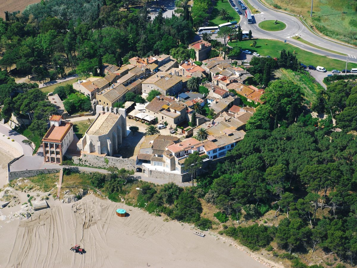 Sant Martí d'Empúries, el primer nucli fundacional de la ciutat grega d'Emporion. La seu del Centre Iberia Graeca es troba a la Casa dels Forestals, l'edifici situat a l'esquerra de l'església (M. Bataller, Arxiu CIG).