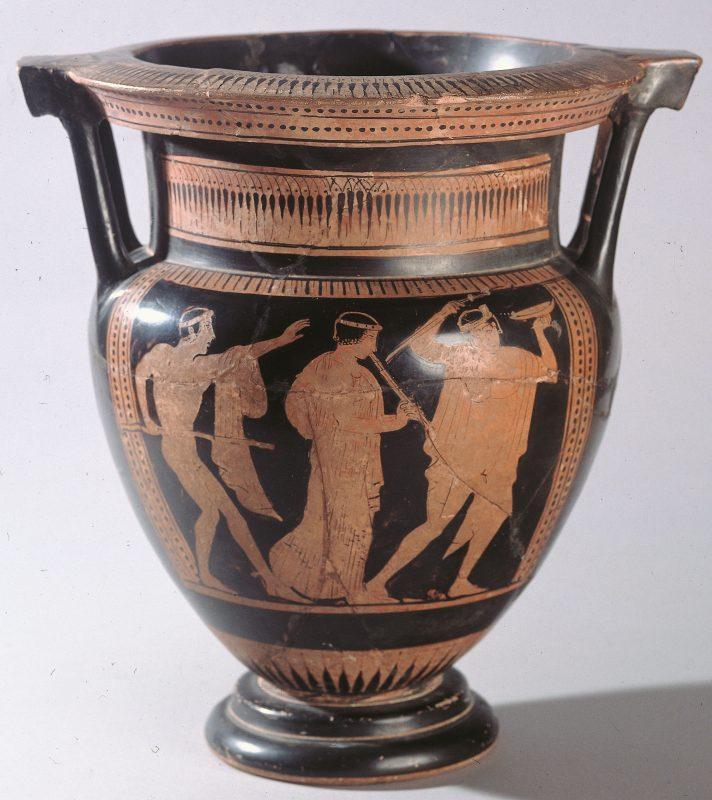 Crater de columnes de ceràmica àtica de figures roges del Pintor d'Agrigent (460-450 aC) procedent d'Empúries, exposat a la seu del MAC-Empúries. Apareix una escena de comos, un passeig festiu que es feia per la ciutat després d'haver participat en un simposi o banquet (Fitxa CIG-3059, Arxiu: MAC-Empúries).