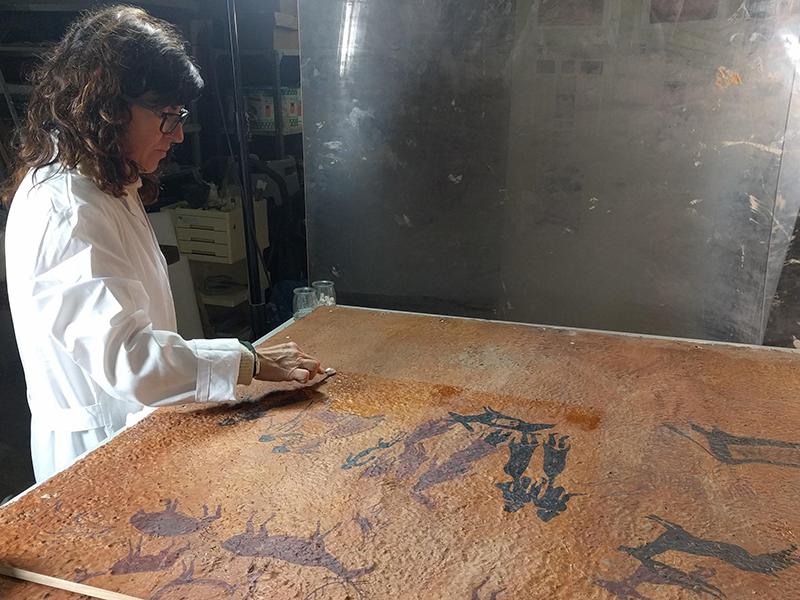 Neteja de l'anvers de la reproducció de les pintures rupestres de la Roca dels Moros. MAC. Conservació-restauració