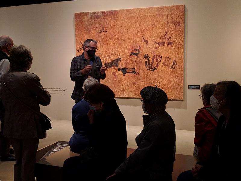 Visita comentada a l'exposició «Art Primer», davant la reproducció de les pintures rupestres de la Roca dels Moros. Irene Garcia