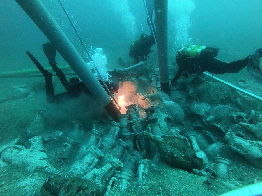 En primer pla, dos arqueòlegs utilitzant les mànegues de succió d'aire i mentrestant, al fons, un altre arqueòleg excavant amb mànega de succió d'aigua.
