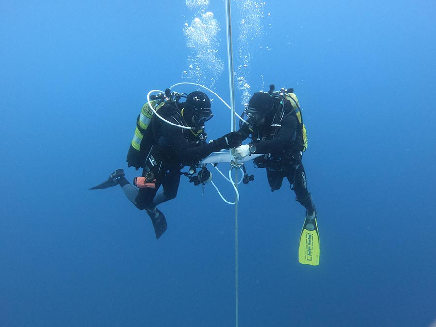 Arqueòlogs aprofitant per prendre notes durant l'última parada de descompressió amb oxigen pur a 6 metres de profunditat