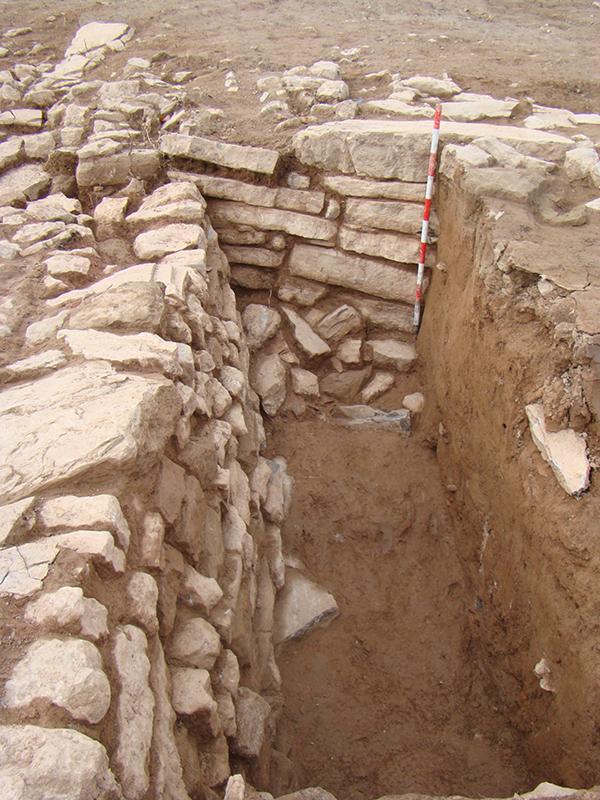 Detall de com la torre (esquerra) s'adossa a la Muralla 3 (al fons). A la dreta, en secció, la terra afegida per crear l'espai d'accés indirecte; foto iPAT Serveis Culturals.